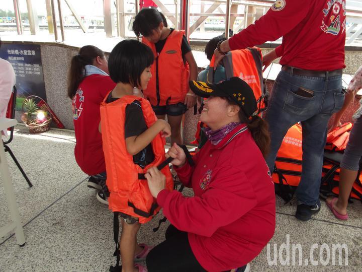 志工媽媽們仔細為小孩子們穿上救生衣。記者謝恩得/攝影