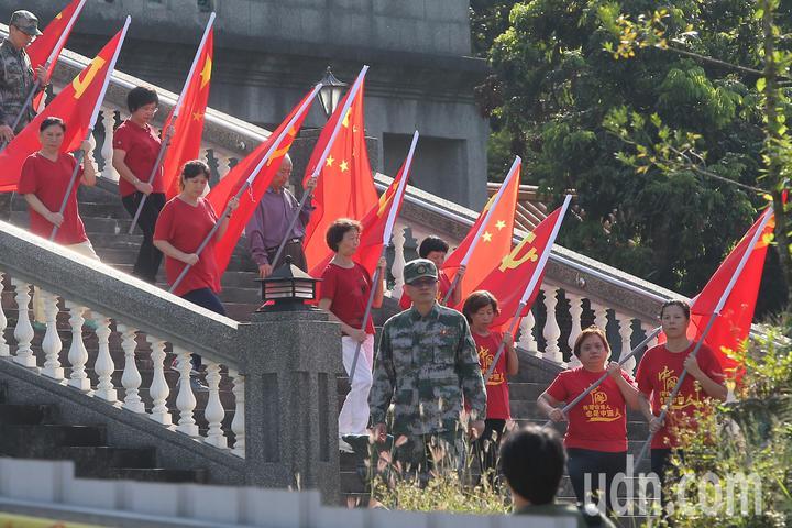 魏明仁(前中)與他的支持者一起舉行「中共愛國主義復興基地」最後一次升降旗典禮後,手持五星旗離開現場。記者黃仲裕/攝影