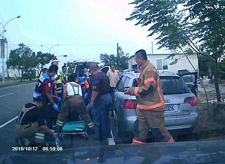 員警擊破車窗後消防員將燒炭男子送醫。 記者周宗禎翻攝