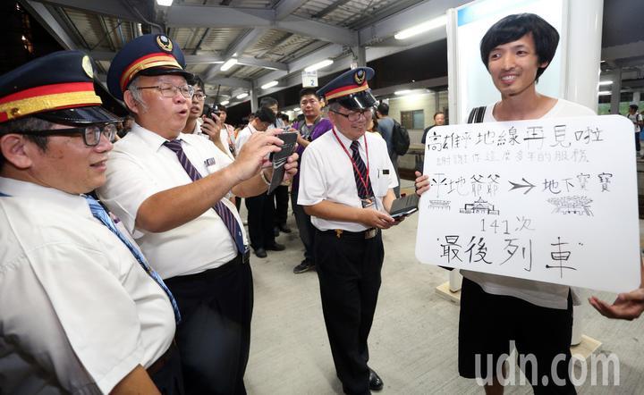 一名鐵道迷自製看板拍照留念,向最後一班列車說再見。記者劉學聖/攝影