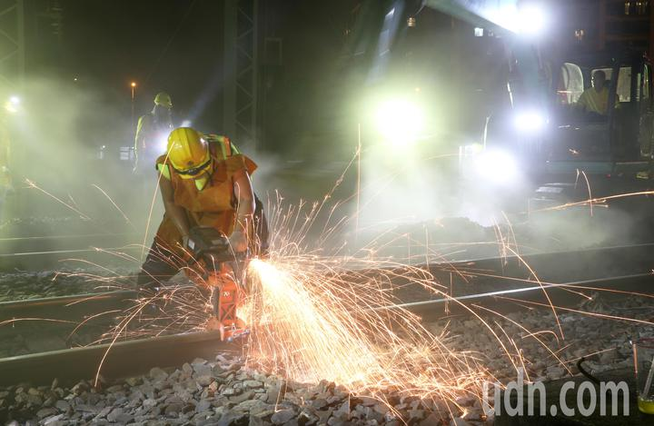 台鐵工程人員加班整備進行左營地下化軌道切換作業,一名工人進行軌道切除作業,冒出大量火花,要趕在天亮前把平面軌道順利切換到地下軌,迎接高雄新站啟用。記者劉學聖/攝影