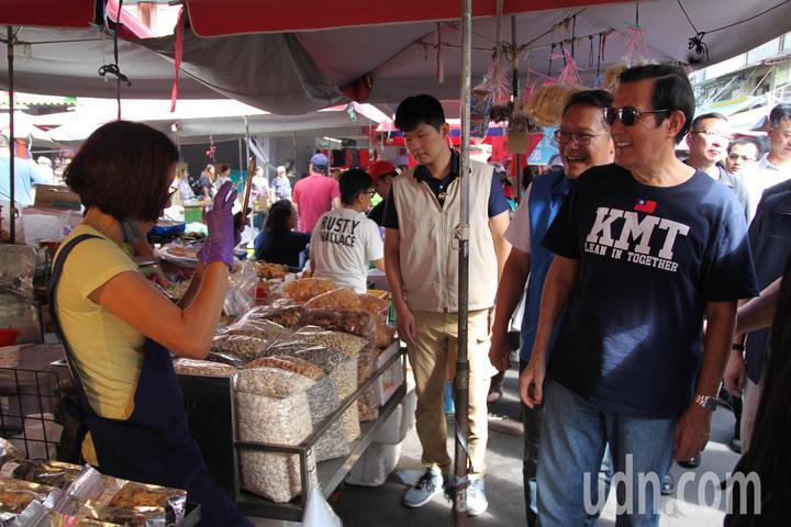 前總統馬英九(右)今到台中市水湳市場拜票時,一位女攤販拿起手機替他拍照,馬英九則調了好姿勢讓女攤眅好好拍。記者黃寅/攝影
