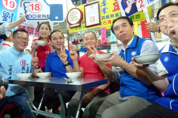 陳學聖(右2)、朱立倫(左3)在市場品嘗羅老闆的手工豆花。記者鄭國樑/攝影