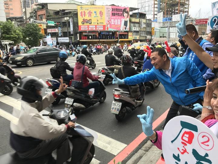 國民黨新北市長候選人侯友宜今天一早到台北橋頭拜票,有機車騎士也熱情的比「2」,表達支持。記者陳珮琦/攝影