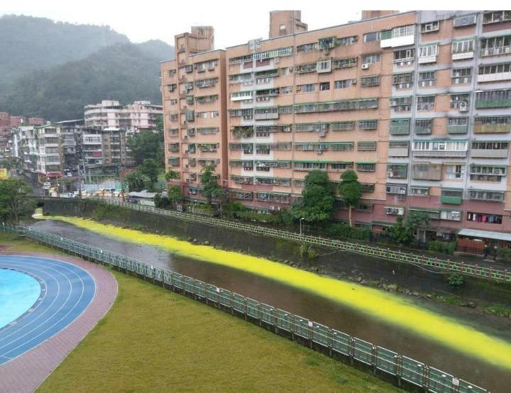 青潭溪因被倒入油漆,導致變成螢光河。圖/王姓居民提供