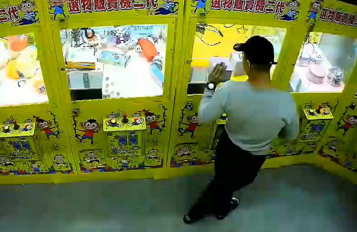 新北市莊姓男子在永和區仁愛路無人看顧的夾娃娃機台店,涉嫌利用強力磁鐵的輔助,偷走娃娃機台內價值1100元的藍芽耳機。圖/警方提供