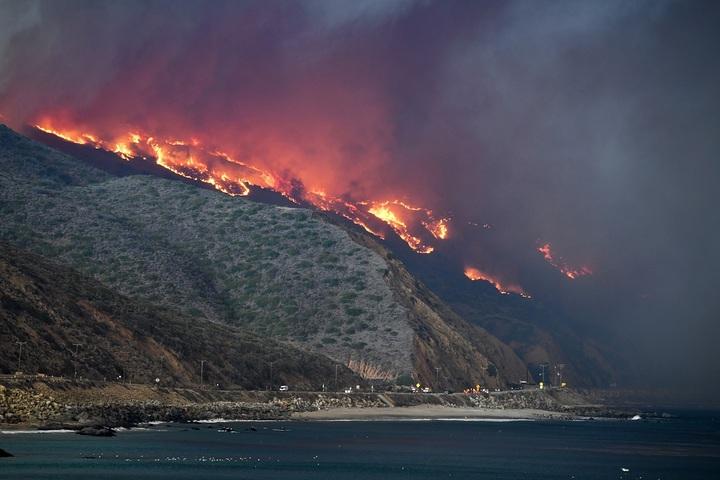 美國加州近日開始吹起強勁炙熱的沙漠風,助長「伍爾希」野火越過101號美國國道直奔太平洋沿岸,富豪名流聚集的馬里布已有部分房舍陷入火海。法新