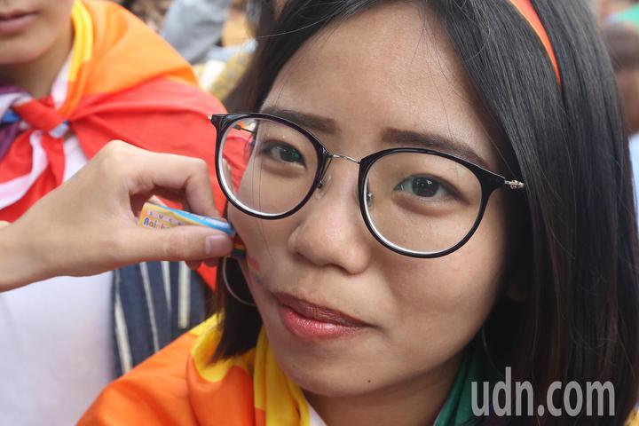 台中同志遊行聯盟今天下午在台中公園舉辦遊行活動,主辦單位在遊行出發前為參與民眾塗上彩虹膠。記者黃仲裕/攝影