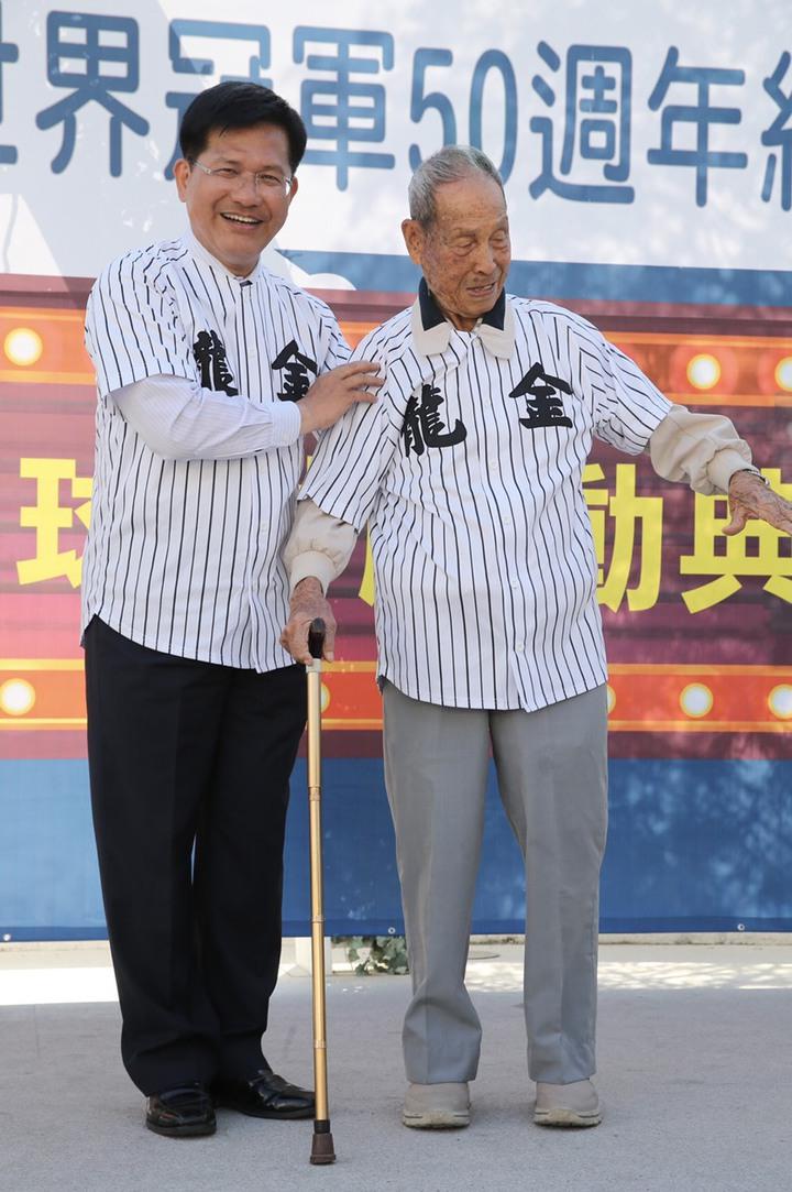 台中市長林佳龍(左)宣佈規劃「洲際棒球村」並慶祝金龍少棒世界冠軍50週年,幫第一代球員棒球長青樹魏來長(右)重披球衣。記者許正宏/攝影