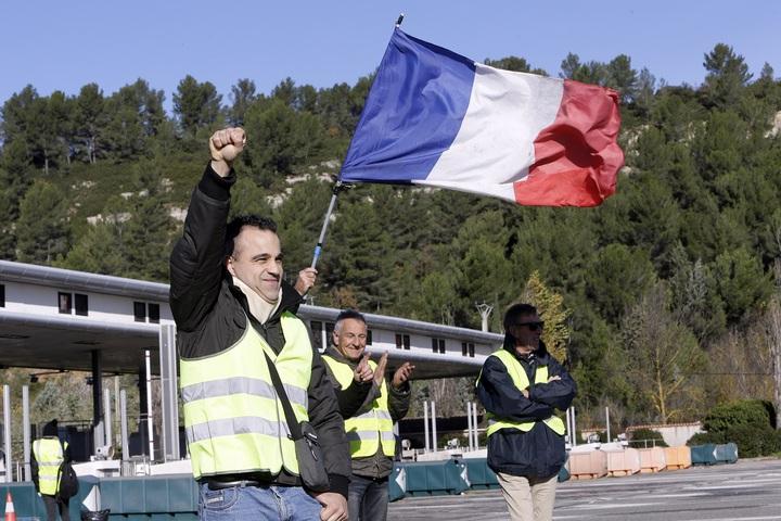 一名穿著反光背心的「黃背心」運動成員4日在法國南部的艾克斯普羅旺斯(Aix-en-Provence)打開高速公路收費站柵欄後高舉拳頭。迫於強大的街頭民意壓力,總理菲力普(Edouard Philippe)宣布燃料稅調漲推遲6個月,並凍結電費與瓦斯費的冬季調漲。美聯