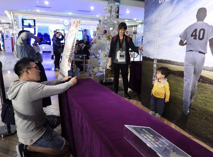 王建民自傳電影「後勁」下午在故鄉台南首映,資深球迷全家捧場,還在看板前拍照留念。記者周宗禎/攝影