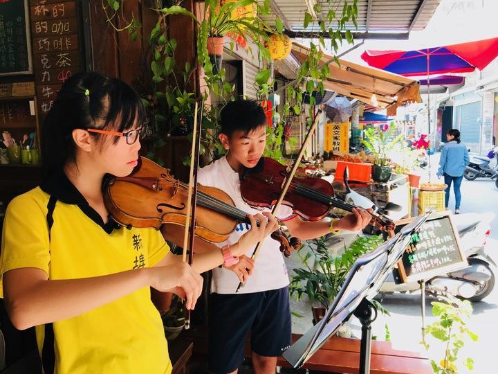 王緯博(右)和一同學琴的夥伴黃靜畬(左),相約在房角石咖啡美學苑店門口進行演奏。記者蔣繼平/攝影