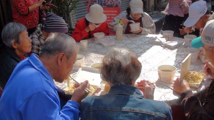 嘉義市愛鄉慈善會今天中午邀請400名街友、弱勢戶聚餐,愛心餐會在西榮街封街舉行,席開40桌。記者王慧瑛/攝影