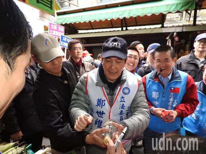 前總統馬英九(右二)今天陪鄭世維(右一)到三重大同南路市場掃街,不少民眾爭相索取春聯、合照、簽名,馬英九也都來者不拒。記者祁容玉/攝影