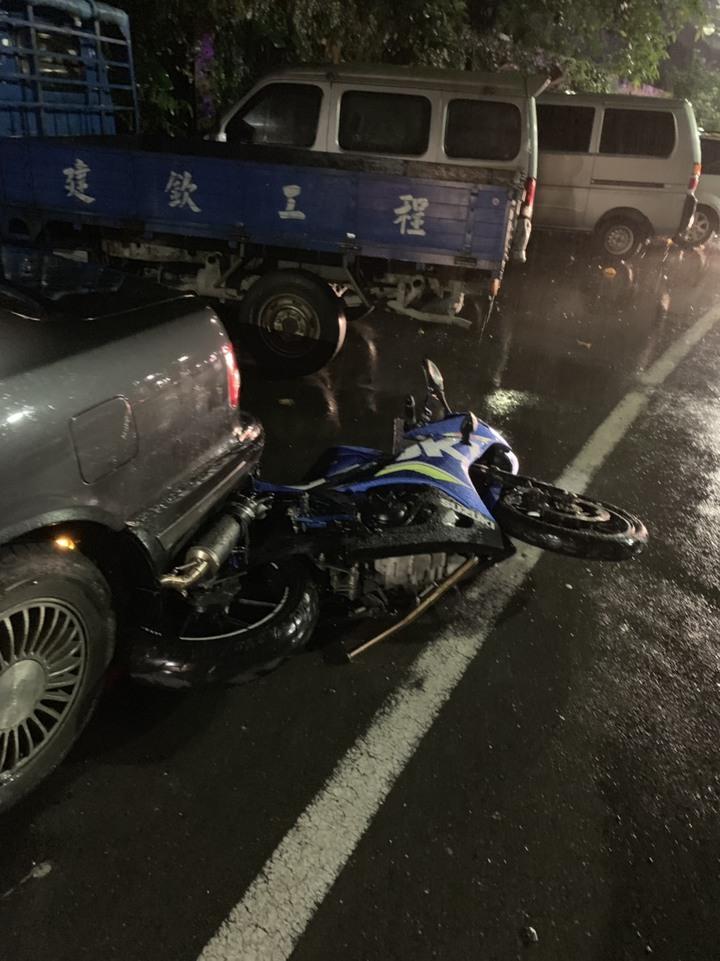 李姓機車騎士凌晨3時許行經暖暖區八堵隧道口時,疑因天雨路滑,不慎自摔撞上安全島,又彈撞停放路旁的自小客車,當場明顯死亡。圖/基隆市警局提供