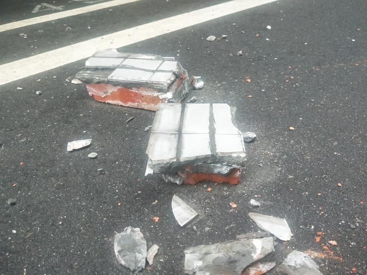 基隆市仁二路、延平街口一棟大樓外牆屋簷突出的部分發生磚磚剝落,整個水泥夾雜十多磚塊往下砸,停在路邊一輛白色轎被砸到,車燈破裂、車頂凹一個洞。記者游明煌/攝影