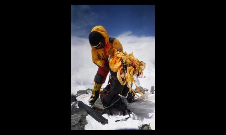高山嚮導次仁旦達因協助清運珠穆朗瑪峰的垃圾,而獲新華社評選為「中國網事•感動2018」年度網絡人物。圖為次仁旦達去年5月在珠穆朗瑪峰7,500米公尺山區撿拾垃圾的畫面。(新華社)