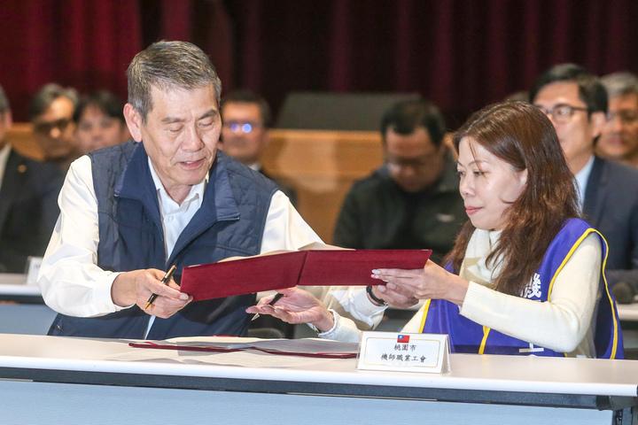華航勞資協議昨晚(14日)落幕,機師工會理事長李信燕(右)與華航總經理謝世謙(左)一起簽約及換約。記者鄭清元/攝影