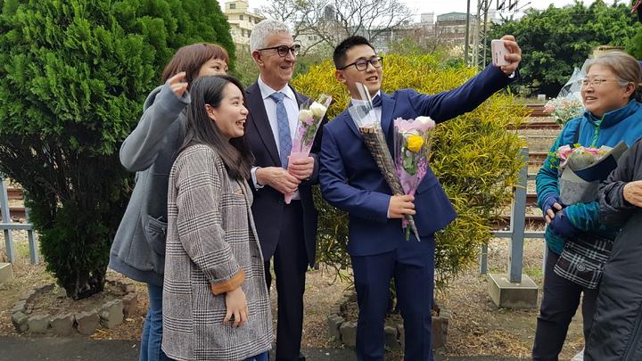 24歲台灣男大畢業生趙守泉與75歲英國男子安迪今天下午在苗栗舉辦婚禮,不少親友與支持者獻花祝福、合影。記者黃瑞典/攝影