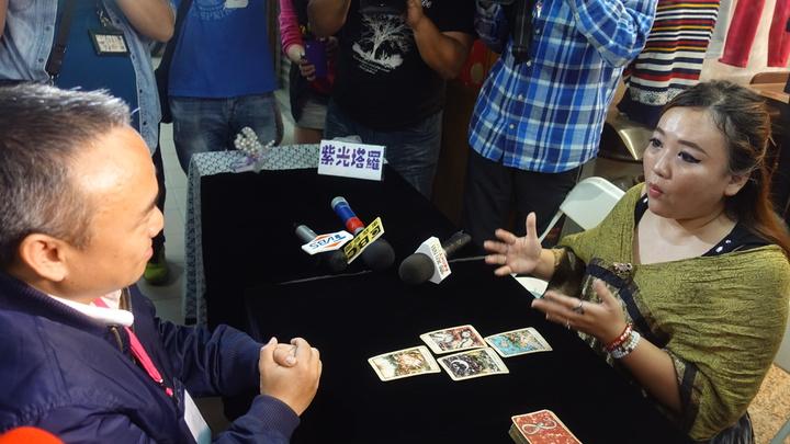 高市觀光局長潘恒旭(左)今出席堀江商圈愛情月系列活動,在堀江商圈的算命攤位體驗算命。記者劉星君/攝影