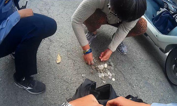 婦人的硬幣掉了一路,路人和員警都幫忙撿錢。記者林保光/翻攝