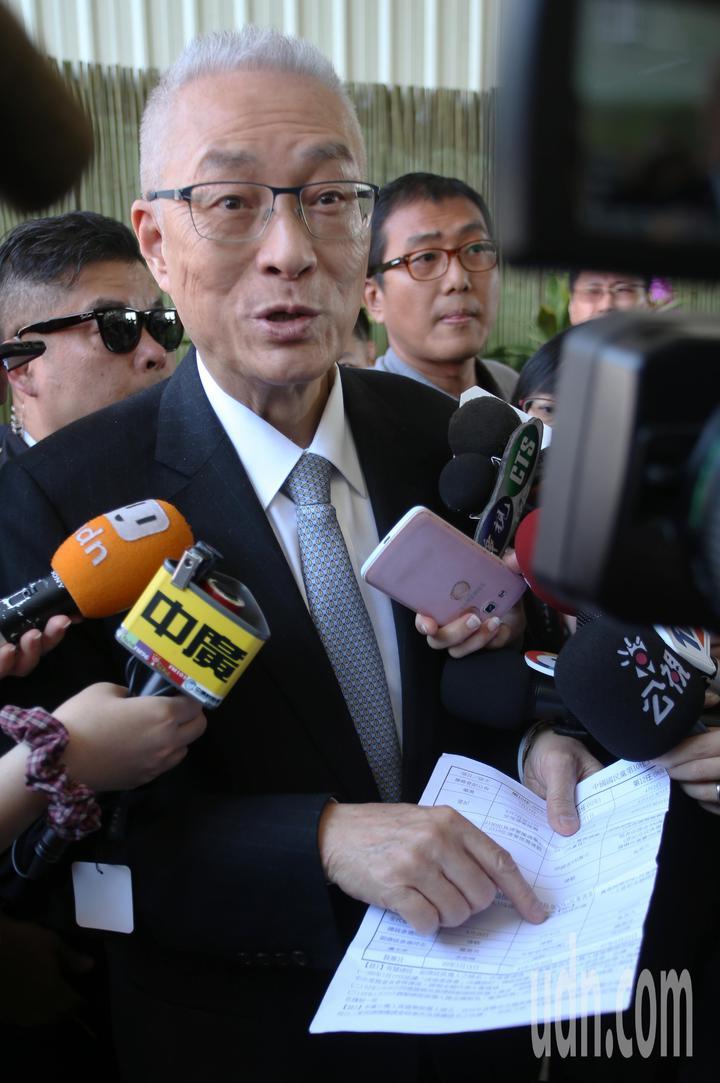 國民黨主席吳敦義到高雄光德寺參加祈福法會,面對媒體詢問立委初選,他拿出預先準備資料說明。記者劉學聖/攝影