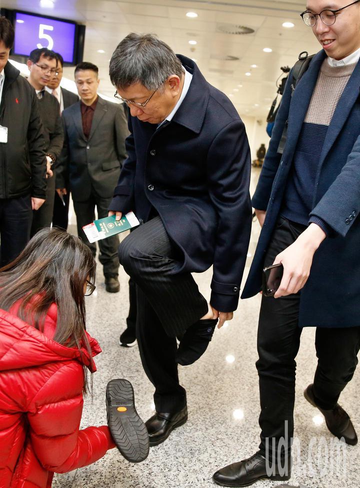 台北市長柯文哲晚上搭機前往以色列參加全球市長會議,將參訪魏茲曼科學院 、新創產業,也會跟有國防背景的國會議員交流,柯文哲準備前往登機時,發現鞋子裡有異物,柯脫下鞋子與襪子,身旁的工作人員幫忙將鞋中的異物倒出。記者鄭超文/攝影