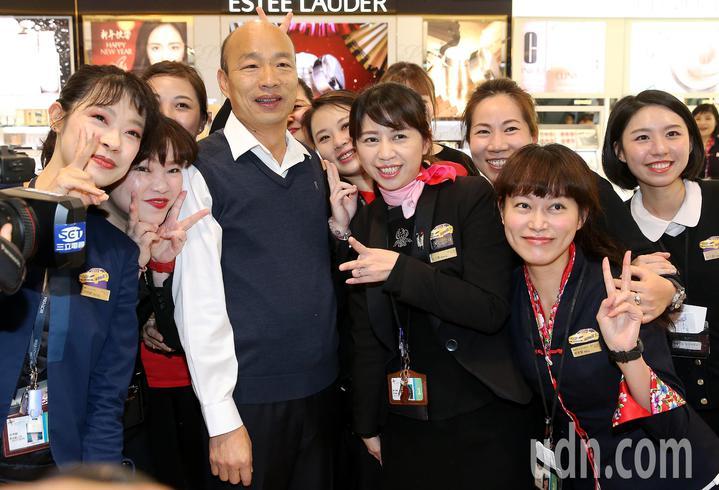 高雄市長韓國瑜(左二)就任後首度出訪,24日清晨率團前往馬來西亞、新加坡等地訪問,登機前與昇恆昌免稅店店員合照。記者陳嘉寧/攝影