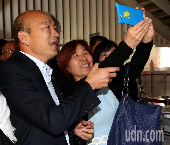 高雄市長韓國瑜(左)結束馬來西亞及新加坡招商訪問行程,28日晚間搭乘中華航空公司班機返抵桃園機場,通關途中應韓粉要求合影。記者陳嘉寧/攝影