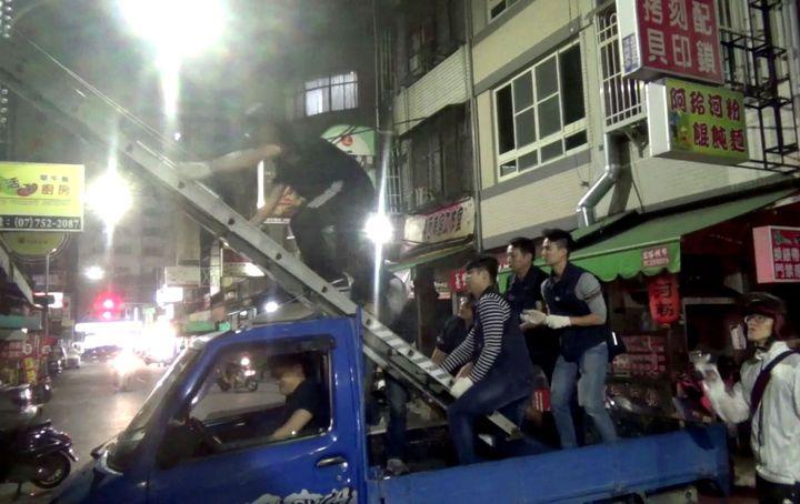 高雄警方以小貨車架梯登樓查緝賭場。記者林保光/翻攝