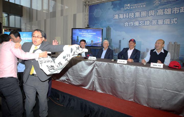 鴻海集團總裁郭台銘今天南下跟高雄市長韓國瑜合體開記者會,律師洪條根(左二)突然拿出要郭台銘選總統的布條鬧場被請出。記者劉學聖/攝影