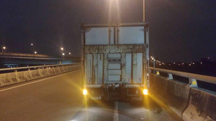 大貨車壓過異物爆胎,車頭還因此受損,只能停放路肩等待救援。記者巫鴻瑋/翻攝
