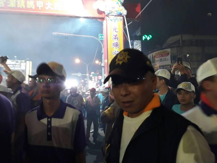 台中市清水警分局刑警,幫輪椅阿公鑽媽祖鑾轎底。圖/警方提供