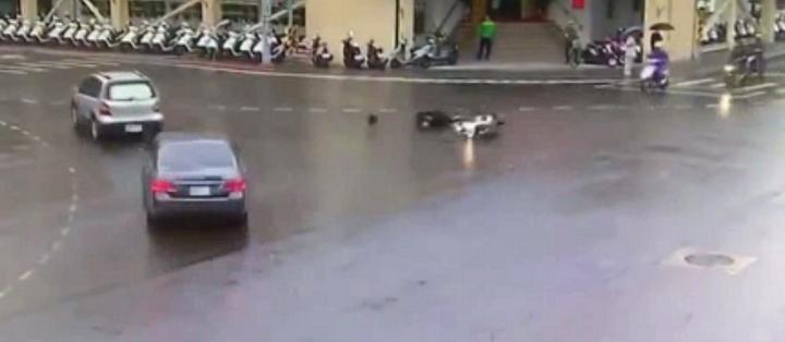 新北市板橋區昨天發生一起嚇人的機車自摔車禍意外,吳姓男子騎車行經板橋警分局前十字路口時,疑似天雨路滑急煞導致連人帶車滑倒,人車滑行約20公尺,撞上一輛準備左轉的汽車。記者王長鼎/翻攝