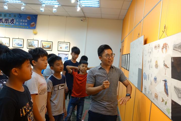 高市林園區第一本生態繪本「倒立水母小非找朋友」繪本繪圖者葉哲翰(右)跟學童們導覽,創作歷程。記者劉星君/攝影