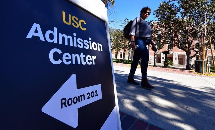 一名女性路過南加州大學(University of Southern California, USC)招生中心的方向指示牌,3月13日攝於美國加州洛杉磯。美國大學入學考試SAT主管單位正考慮引進新措施「逆境分數」,以充分反映考生家庭的社會經濟背景。法新