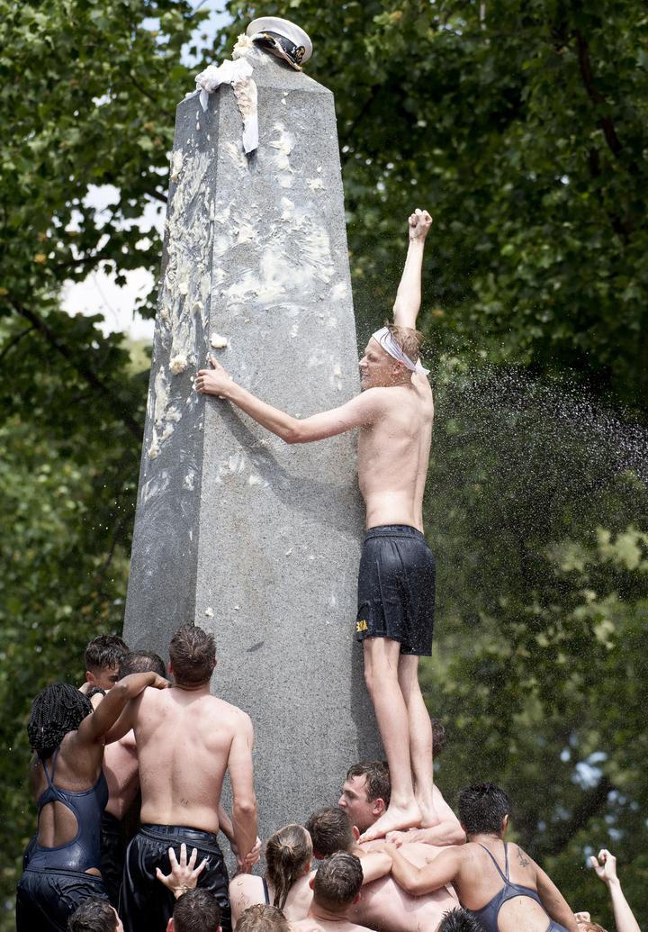 美國海軍官校20日舉行傳統的「赫恩登紀念碑攀爬儀式」,讓一年級新鮮人藉由攜手合作,奮力攀登塗滿植物油的紀念碑,以軍官大盤帽替換水手帽,來證明他們有資格告別菜鳥身分。美聯社
