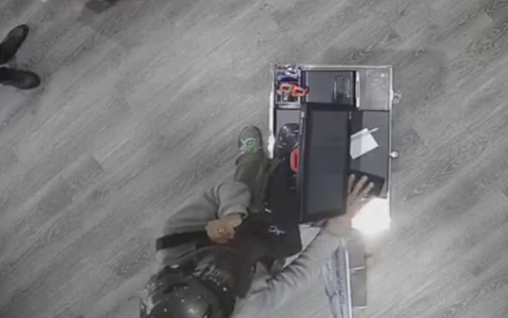 頭戴深色安全帽的林男到飲料店不點飲料,以隨身包包掩護行竊櫃台上手機。記者林佩均/翻攝