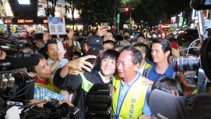鴻海董事長郭台銘今晚逛逢甲夜市,有支持者與郭台銘貼臉自拍。記者洪敬浤/攝影