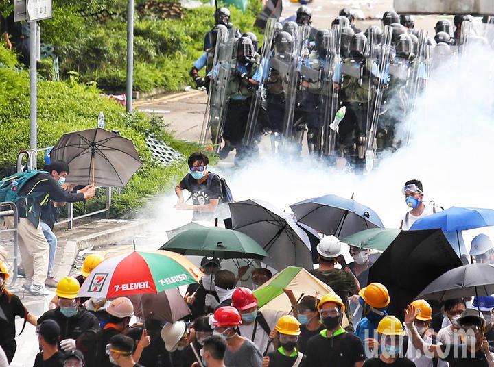 警方正不停發射催淚瓦斯,試圖驅散「違法集結」的示威群眾,群眾以傘抵擋向後撤退。特派記者王騰毅/攝影