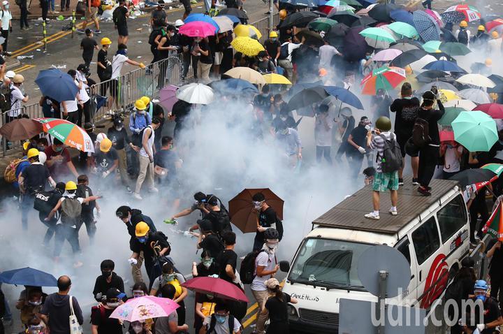 警方不停發射催淚瓦斯,試圖驅散「違法集結」的示威群眾,部分民眾咳嗽與掩住口鼻。特派記者王騰毅/攝影