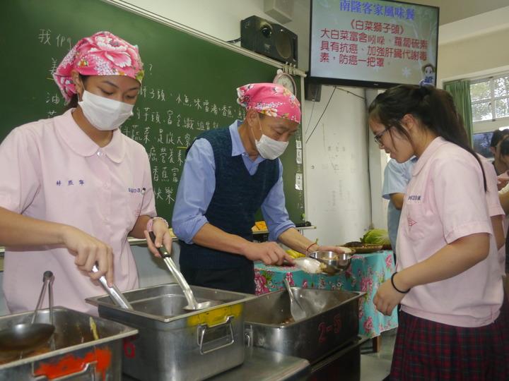高雄市長韓國瑜戴頭巾、口罩,替學生分配主食油飯。記者徐白櫻/攝影