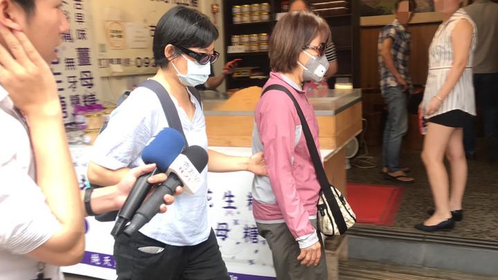 江明學的姊姊(紅衣)與牧師(藍衣)到場進行指認,面對媒體詢問全程不發一語。記者柯毓庭/攝
