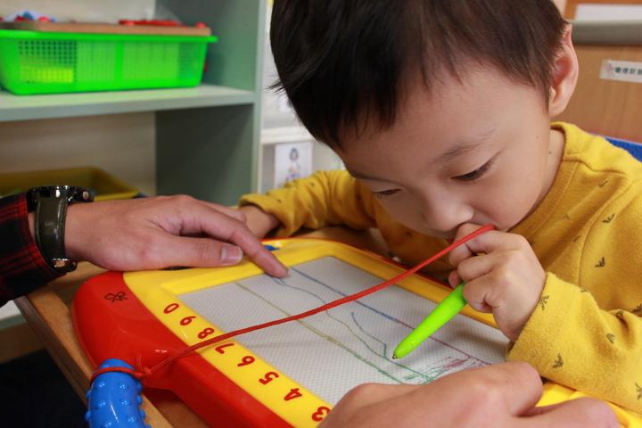 阿邦接受早療3年,學會塗鴉,生活技能不斷升級。圖/心路基金會提供