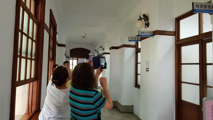 一隻領角鴞飛進新竹市府停在2樓走廊燈具上,可愛模樣吸引市府員工及洽公民眾拍照。記者黃瑞典/攝影