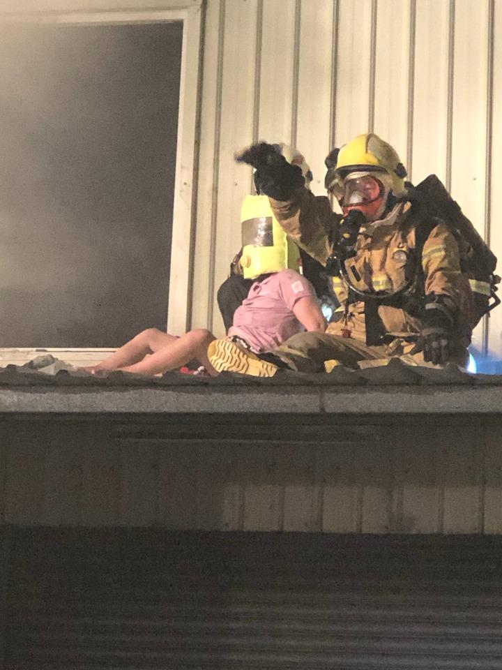 消防人員搶進二樓火場救出受困人員,並為她戴上氧氣面罩 。記者蔡維斌/攝影