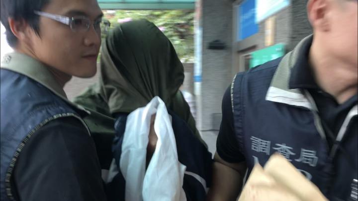 涉案劉姓巡佐(中)上午被帶到彰化地檢署,頭、手以外套遮掩。記者林敬家/攝影