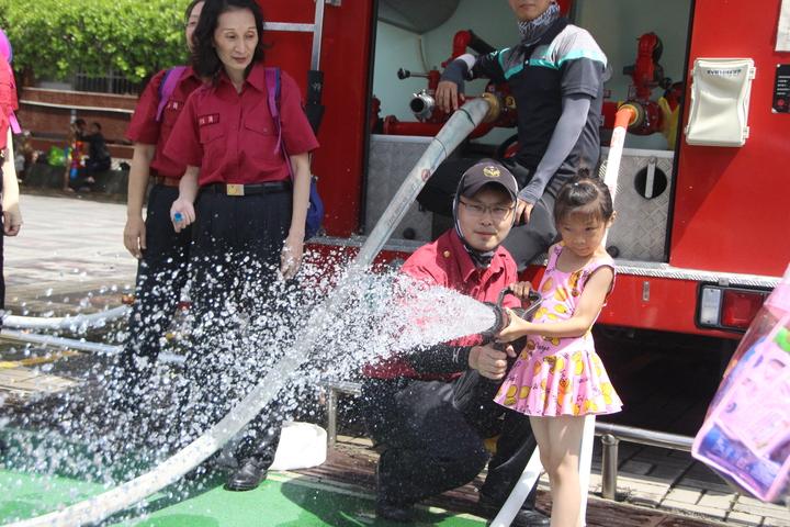 小朋友體驗操作消防水瞄。記者林敬家/攝影