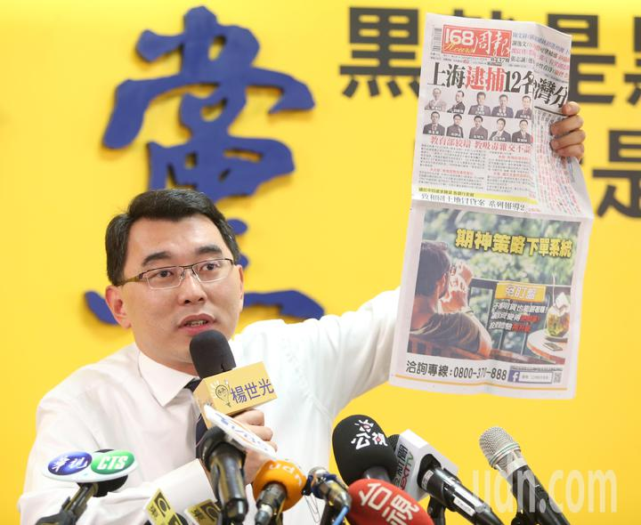楊世光出示上海逮捕台灣分析師的新聞,報紙下方是仟和億子公司販售的投資下單軟體。記者侯永全/攝影