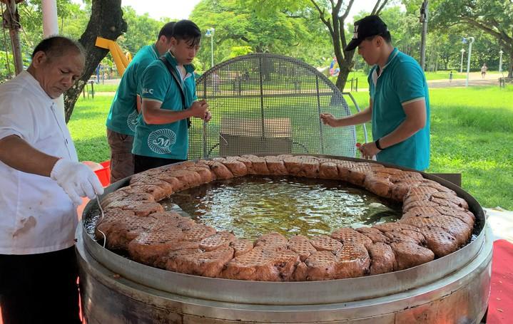 麥順英帶領團隊製作重達30公斤的超大甜甜圈,一起鍋就吸引眾人目光。記者翁禎霞/攝影